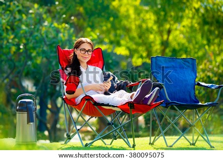 Pretty woman spending time outdoors, sitting in armchair with phone in hands, enjoying vacation in the camping, relaxation in countryside - stock photo