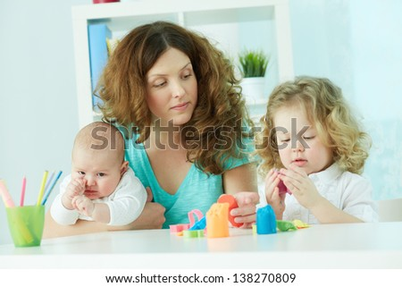 Pretty woman spending time with her children at home - stock photo