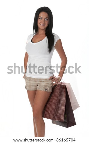 Pretty woman standing, holding shopping bags. White background. - stock photo