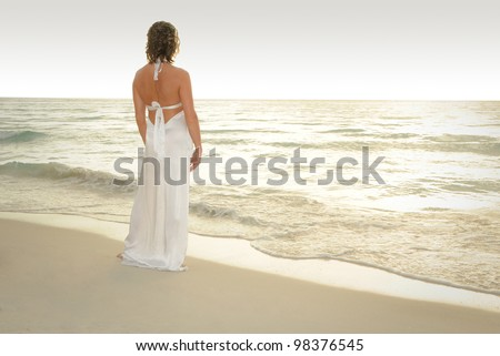 Pretty Woman standing on a white sand beach of a paradise island in a white evening gown looking out at the ocean - stock photo