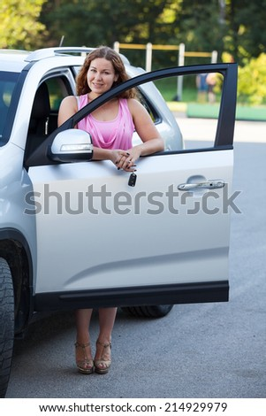 Pretty woman standing side of car with opened door - stock photo