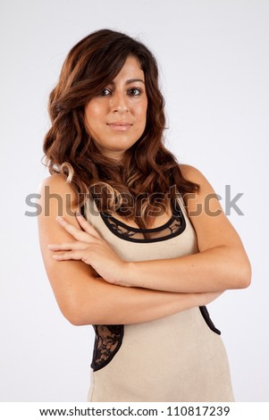 Pretty woman standing with her arms crossed and looking at the camera with a thoughtful, pensive expression - stock photo