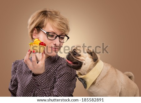 Pretty woman stopping her dog from eating cake - stock photo
