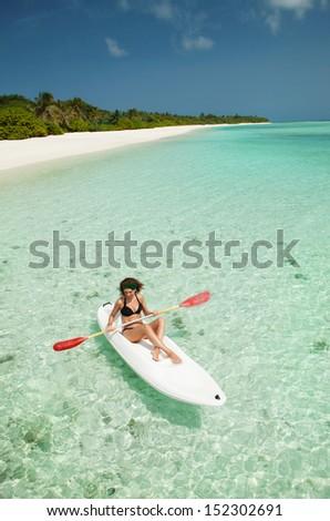 Pretty woman swimming in the canoe - stock photo