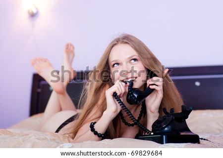 Pretty woman talking by the telephone on a bed in bedroom, dressed in a linen and beads