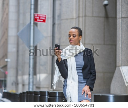Pretty Woman texting on street. Dressing in a woolen cropped jacket, a fitted dress, a long scarf, a young black fashion girl is sitting on a metal column outside, checking messages on a mobile phone. - stock photo