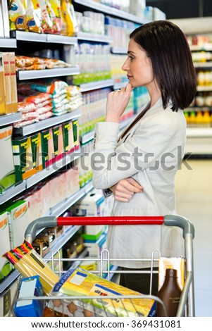 Pretty woman thinking with hand on chin in supermarket