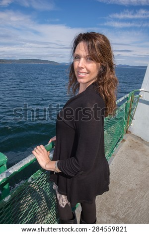 Pretty woman traveling on a ferry boat over the ocean - stock photo