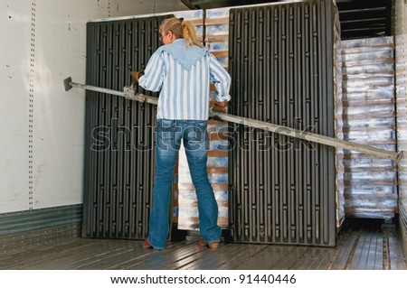 Pretty woman truck driver placing a load-lock on the inside of her trailer. This secures the loaded pallets from shifting during transportation. - stock photo