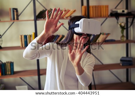 Pretty woman trying to push something while wearing white virtual reality headset glasses - stock photo