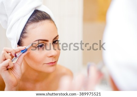 Pretty woman tweezing her eyebrows in the mirror.