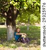 pretty woman under big tree in sunny day - stock photo