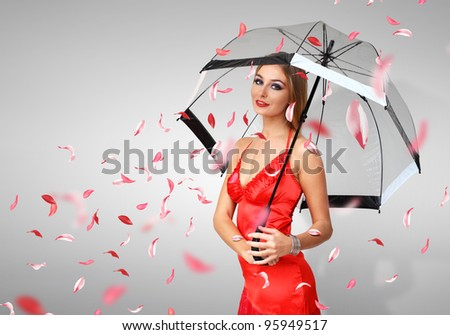 Pretty woman under umbrella with red petals around