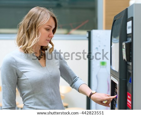 Pretty woman using coffee vending machine.