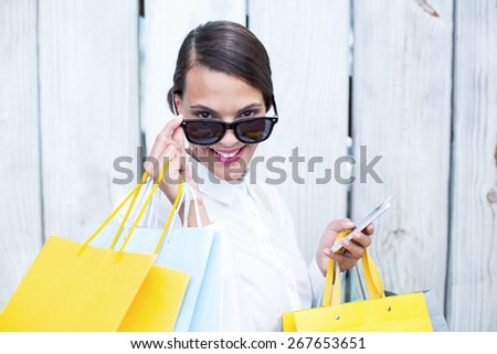 Pretty woman using her smartphone holding shopping bags in front of wooden grey planks - stock photo