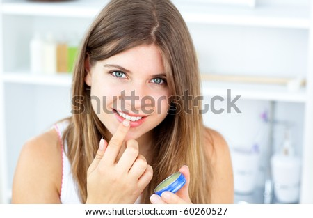 Pretty woman using vaseline for her lips in the bathroom at home