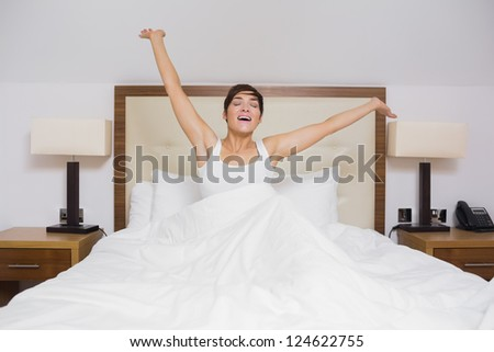 Pretty woman waking up in hotel room and stretching - stock photo