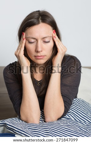 Pretty woman waking up with headache  - stock photo