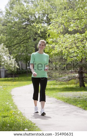 Pretty woman walking in the neighborhood listening to music on her MP3 player - stock photo
