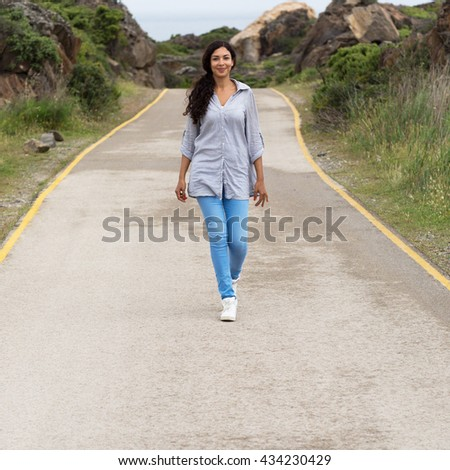 Pretty woman walking on a street in natural parc - stock photo