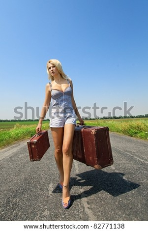 Pretty woman walking on the road with her baggage - stock photo