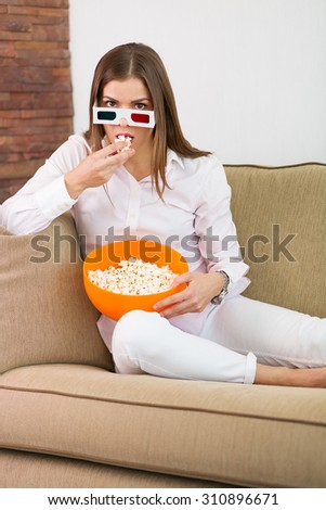 Pretty woman watching movie in 3D glasses - stock photo