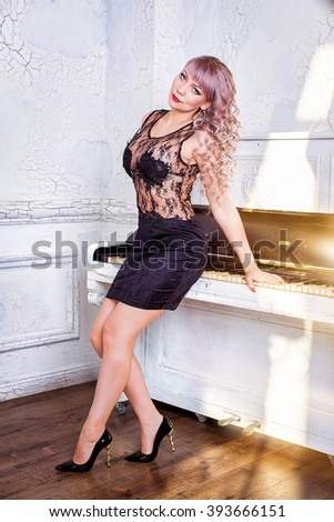 pretty woman wearing a black elegant dress , with blond wave hair , posing near a pianoforte - stock photo