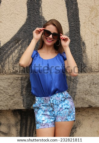 Pretty woman wearing a blue dress posing on the wall - stock photo