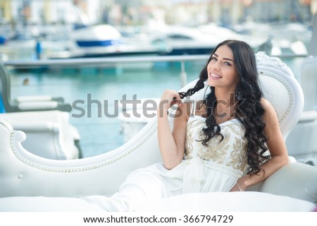Pretty woman wearing beautiful elegant dress, enjoying a relaxed sunny day out at a marina, with boats as background. Beautiful sunset at the yacht club - stock photo