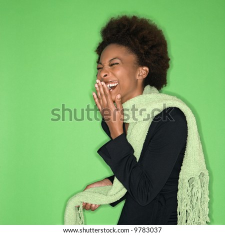 Pretty woman wearing green scarf laughing against green background.