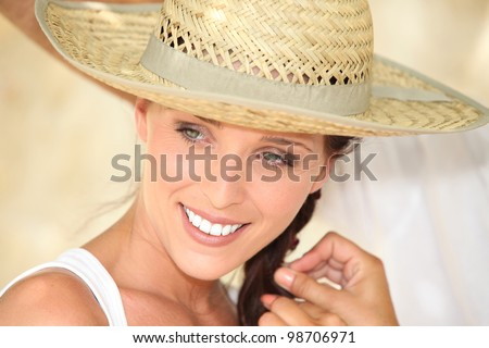 Pretty woman wearing straw hat - stock photo