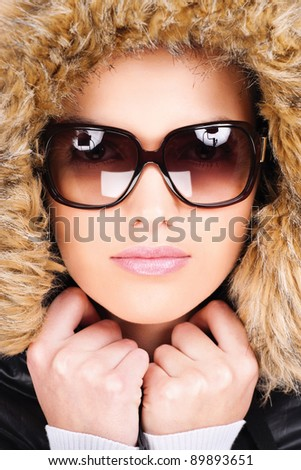 pretty woman wearing winter outfit with fur and glasses - stock photo