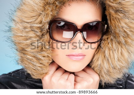 pretty woman wearing winter outfit with fur and glasses