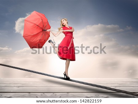 Pretty woman with a broken umbrella over the clouds standing on a rope