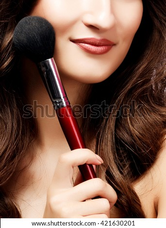 Pretty woman with a makeup brush