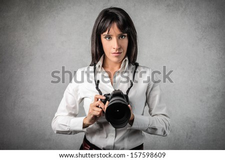 pretty woman with a professional camera - stock photo
