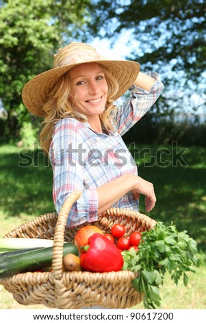 Pretty woman with a straw hat and basket of vegetables.