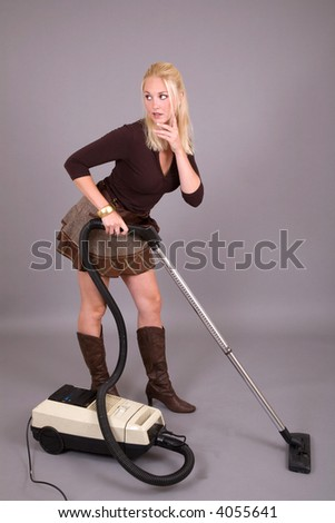 Pretty woman with a vacuumcleaner standing looking a bit puzzled - stock photo