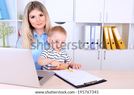Pretty woman with baby working at home - stock photo
