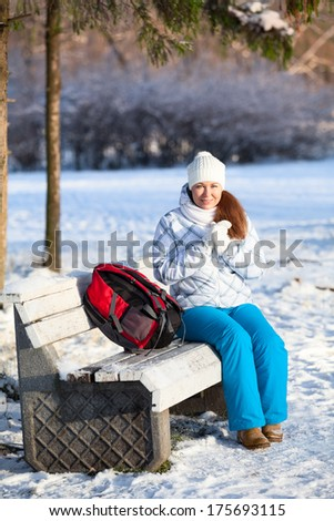Pretty woman with backpack resting on a bench in winter park - stock photo