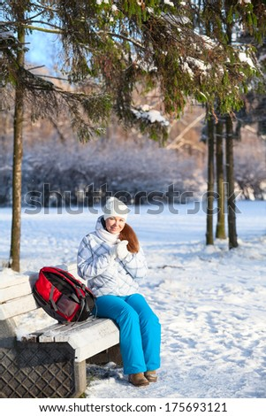 Pretty woman with backpack sitting on a bench in winter park - stock photo