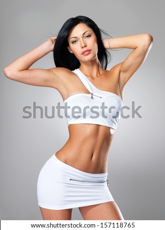 Pretty woman with beautiful slim tanned body - posing at studio on gray background - stock photo