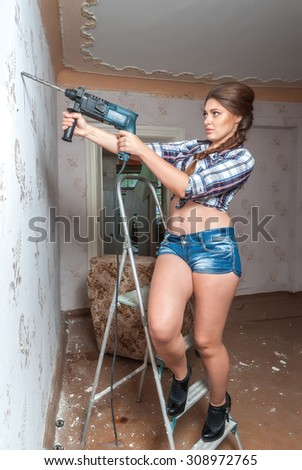 Pretty woman with building puncher drilling hole in wall - stock photo