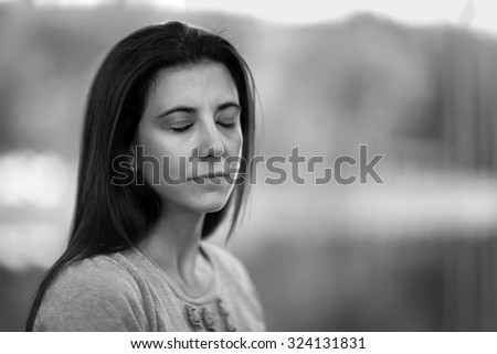 Pretty woman with eyes closed black and white portrait - stock photo