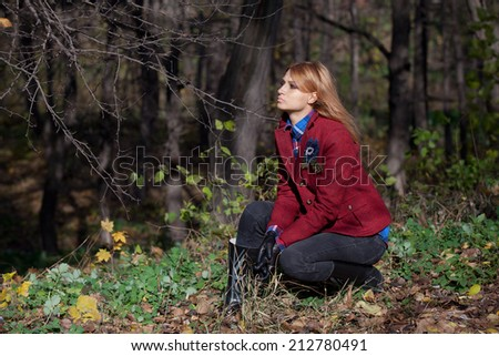 Pretty woman with flowing hair in tweed jacket and leather gloves sitting at grass in autumn forest - stock photo
