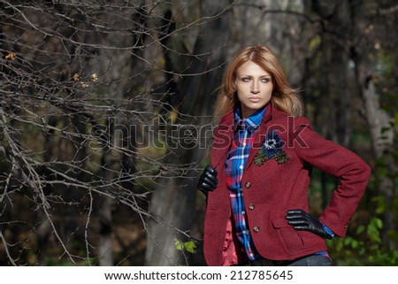 Pretty woman with flowing hair in tweed jacket and leather gloves walking and posing in autumn forest - stock photo
