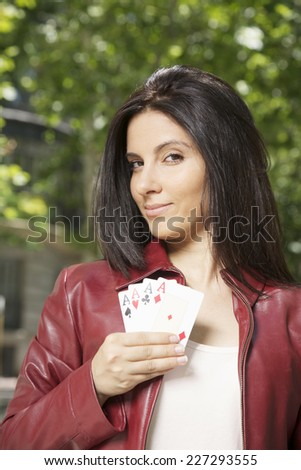 pretty woman with four aces in her hand  - stock photo