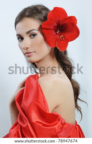 pretty woman with fresh red flower in the hear after spa procedures - stock photo