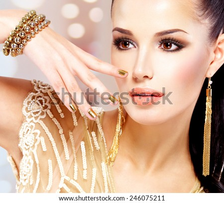 Pretty woman with golden nails and beautiful gold jewelry isolated on white background - stock photo