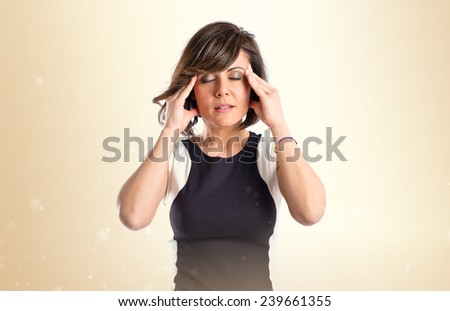 Pretty woman with headache over isolated ocher background  - stock photo